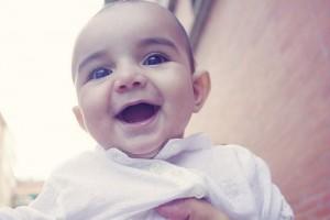 Bebé riendo en brazos de su mamá