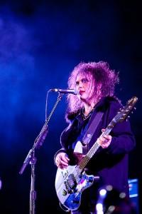 Inconfundible estética de Robert Smith, voz y guitarra de The Cure