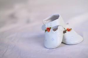 Elegantes merceditas de bebé en color blanco, con velcro y con una flor de color rojo