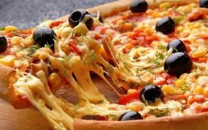 Sabrosa pizza de verduras, aceitunas negras y queso fundido