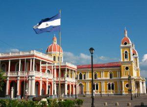 Bandera nicaraguense junto a La gran Plaza de la Independencia y La Catedral amarilla de cúpulas de tejas rojas